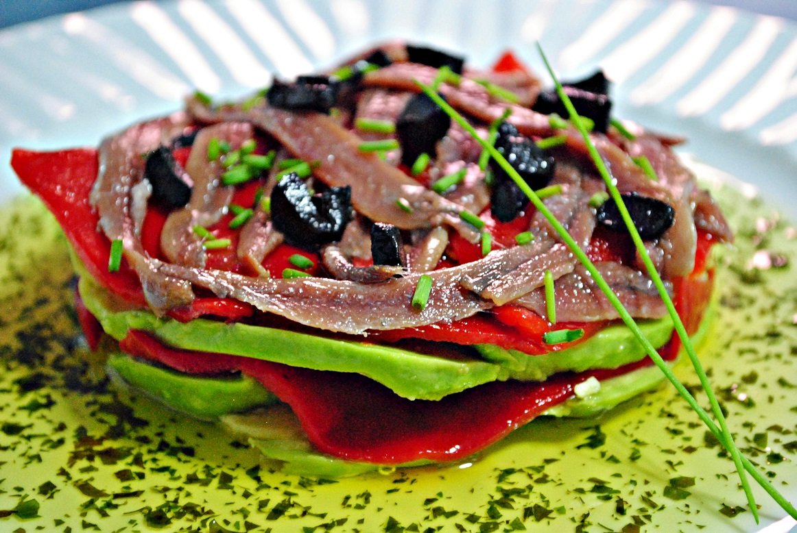 Avocado with anchovies, piquillo peppers and black garlic